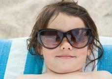 A menina toma sol na praia Fotos de Stock Royalty Free