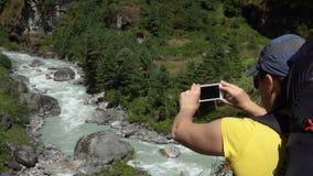 A menina toma uma foto da natureza pelo telefone filme