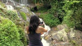 A menina toma uma imagem de uma cachoeira em um telefone celular filme