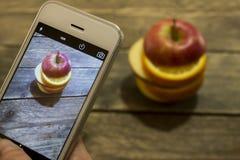 A menina toma uma imagem de uma maçã cortada em uma tabela de madeira Imagens de Stock Royalty Free