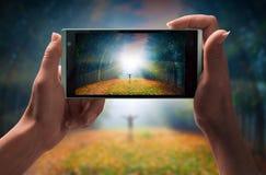 A menina toma uma imagem do homem em uma floresta imagens de stock