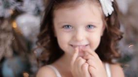 Menina três anos velha em um sorriso branco do vestido filme