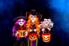 Menina três bonita em um traje da bruxa em um fundo escuro no fumo que scaring e que faz as caras imagens de stock