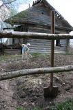 A menina trabalha o solo perto de uma cabana rústica de madeira abandonada, Rússia rural Fotografia de Stock