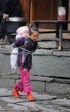 Menina tradicional pobre que se importa a criança na vila velha em China Fotografia de Stock