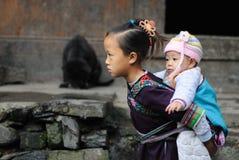 Menina tradicional pobre que se importa a criança na vila velha em China Imagem de Stock