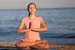 A menina trata a ioga no oceano da praia Fotos de Stock