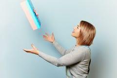 A menina trava as mãos de um presente em um fundo azul Imagens de Stock