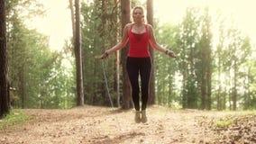 A menina treina com uma corda de salto em um parque do verão no por do sol Jovem mulher que faz esportes fora Movimento lento video estoque