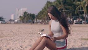 A menina tremenda no vestido leve lê o livro que senta-se na areia video estoque