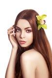 Menina triguenha bonita. Cabelo longo saudável com flor da orquídea foto de stock royalty free