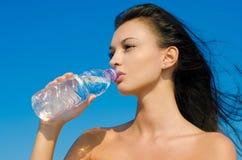 Menina triguenha bonita que bebe de um frasco de Fotos de Stock