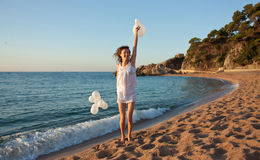 Menina triguenha de sorriso feliz com na praia ensolarada Fotografia de Stock Royalty Free