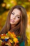 Menina triguenha e folhas douradas Fotografia de Stock Royalty Free