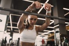 Menina triguenha nova atl?tica vestida no sportswear que tem o resto ao lado do barbell no gym moderno foto de stock royalty free