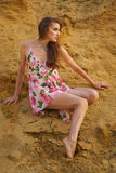 Menina triguenha nova bonito no vestido pela areia Foto de Stock