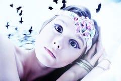 Menina triguenha Scared na cama com corvos imagem de stock royalty free