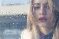 A menina triste bonita com olhos grandes em um revestimento é atrás do vidro molhado Fotografia de Stock Royalty Free