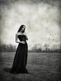 A menina triste bonita do goth está no campo outonal Efeito da textura do Grunge imagem de stock