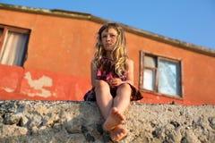A menina triste bonita pequena senta-se perto da construção velha Fotografia de Stock