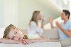 A menina triste com luta parents no fundo Imagens de Stock Royalty Free