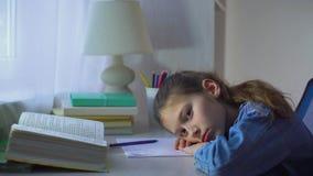 A menina triste da escola pôs sua cabeça sobre as mãos e vista na câmera vídeos de arquivo