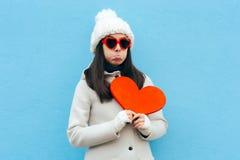 Menina triste desolada da virada que guarda um coração no fundo azul fotografia de stock