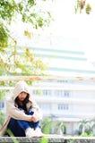 A menina triste do adolescente comprimiu o assento no assoalho de uma ponte fotografia de stock royalty free