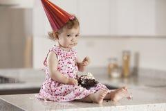 Menina triste do aniversário que come o bolo Foto de Stock Royalty Free