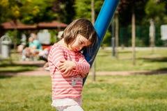 A menina triste está ao lado de um balanço no campo de jogos Fotos de Stock Royalty Free