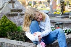 Menina triste na frente da sepultura Imagem de Stock