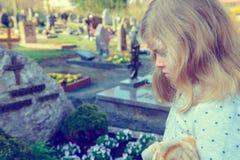 Menina triste na frente da sepultura Imagens de Stock