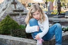 Menina triste na frente da sepultura Fotografia de Stock Royalty Free