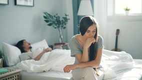 Menina triste nos pijamas que sentam-se no indivíduo sighing de pensamento do quando da cama que dorme em casa video estoque