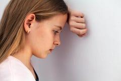 Menina triste nova do adolescente que sustenta sua cabeça contra a parede Fotografia de Stock Royalty Free