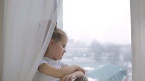 A menina triste olha para fora a janela, pensa sobre algo e sentencia-o vídeos de arquivo