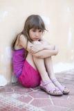 Menina triste pequena com o cabelo longo que senta-se abraçando seus joelhos Imagens de Stock