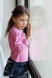 A menina triste pequena olha para fora o indicador Fotografia de Stock