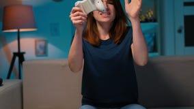 A menina triste perde o jogo de vídeo em casa na noite Mulher excitada do gamer que senta-se em um sofá, jogando e perdendo no ví filme