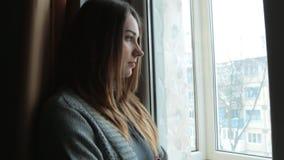 Menina triste perto da janela que pensa sobre algo video estoque