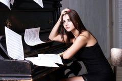 Menina triste perto do piano Fotos de Stock Royalty Free