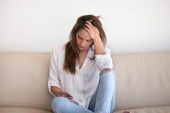 Menina triste que guarda a mensagem de espera do smartphone do noivo imagens de stock royalty free
