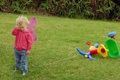 Menina triste que joga com triciclo colorido fotografia de stock royalty free