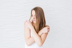 A menina triste que não olha a câmera com seus braços cruzou-se sobre sua caixa com seus antebraço que cobrem seus peitos Foto de Stock