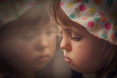 Menina triste que olha através da janela fotos de stock royalty free