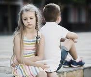 Menina triste que senta-se de volta ao amigo exterior fotografia de stock