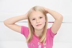 Menina triste que senta-se em uma cama no quarto Imagens de Stock Royalty Free
