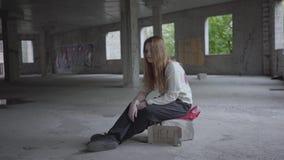 Menina triste que senta-se em uma sala vazia empoeirada grande na construção abandonada, sente má Um sinal que diga a ajuda e o f filme