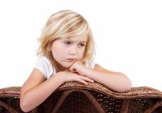 Menina triste que senta-se na cadeira Fotos de Stock