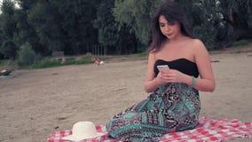 Menina triste que senta-se na praia e que olha o telefone celular vídeos de arquivo